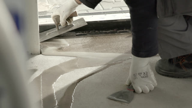 applying liquid resin on cracked cement floor - pavimento video stock e b–roll