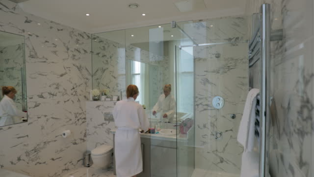 stockvideo's en b-roll-footage met toepassing van make-up in hotel badkamer - domestic bathroom