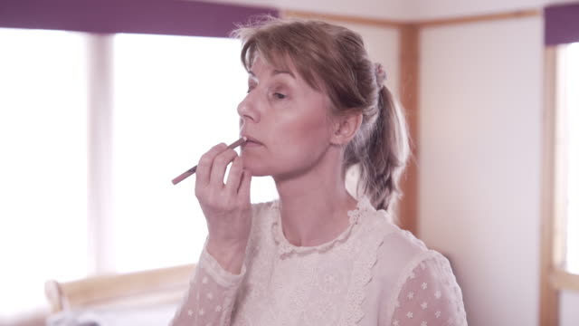 applying make-up in the bedroom - lip liner stock videos & royalty-free footage