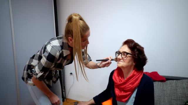 vídeos de stock, filmes e b-roll de aplicando a maquiagem na senhora sênior - blush