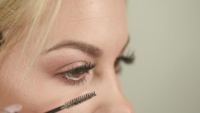 Applying mascara on eyelashes