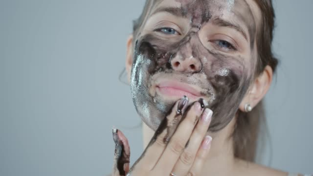 applying peel off mask on face - facial mask beauty product stock videos and b-roll footage