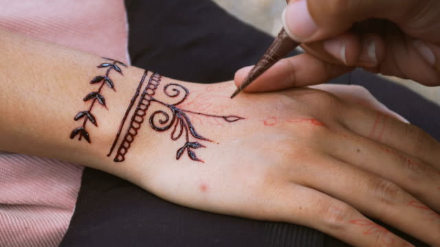 applying simple henna paint onto back of hand - mandala stock videos & royalty-free footage