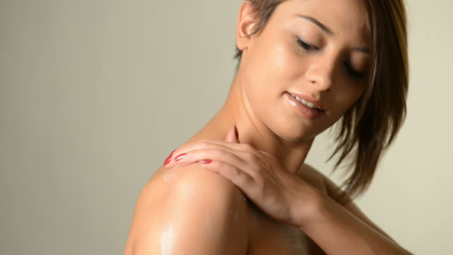 Applying skin cream to a bare shoulder