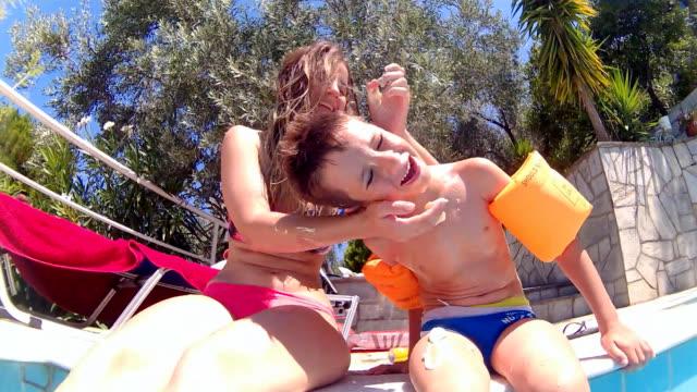 anwendung von sonnencreme - schwimmflügel stock-videos und b-roll-filmmaterial