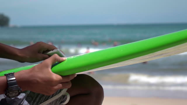 Applying wax on a surfboard