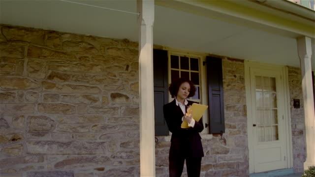 appraiser walking under veranda and examining exterior of stone house - examining stock videos & royalty-free footage
