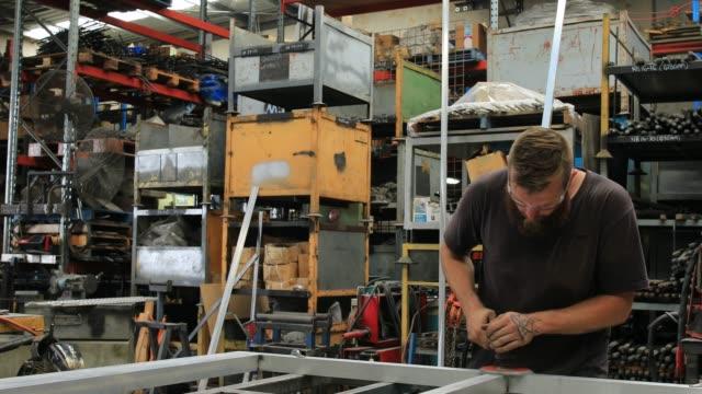 stockvideo's en b-roll-footage met leerling metalen werknemer met machtshulpmiddel in fabriek - aluminium
