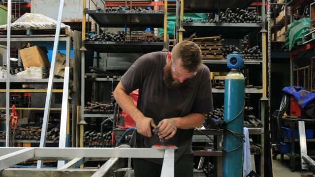 Apprentice Metal Worker Using Power Tool In Factory