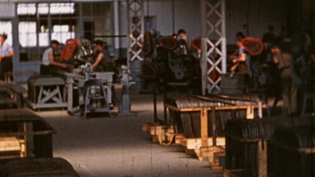 Apprentices using various machines while working in large metal works shop at National Youth Administration camp during WWII