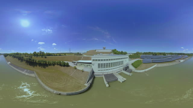 AERIAL VR 360: Approaching and flying over the hydroelectric power plant on a sunny day