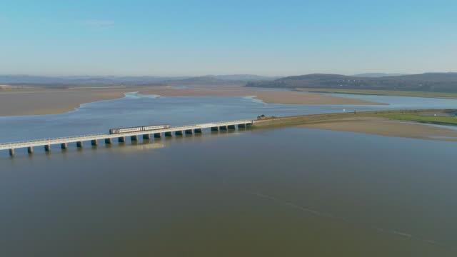 approaching arnside across railway train viaduct 4k aerial drone film - viaduct stock videos & royalty-free footage