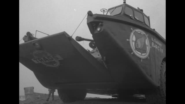 vidéos et rushes de approaching beach, soldiers standing at end of landing barge on beach loaded with supplies / two shots of barc landing on beach, its ramp slightly... - véhicule amphibie