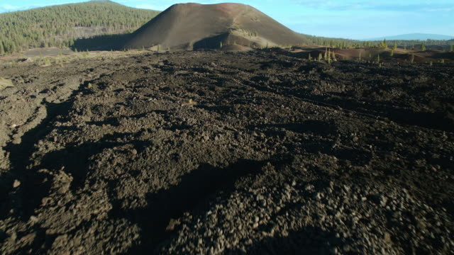 approaching cinder cone volcano over rocky lava beds in lassen volcanic national park. - kegel stock-videos und b-roll-filmmaterial