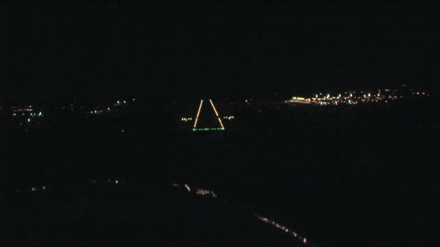 aerial pov approaching runway and landing lights of airport at night / darwin, australia - airport runway stock videos & royalty-free footage