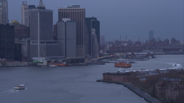 approaching skyscrapers of the financial district in lower manhattan at dusk, ferries docking at terminal. shot in 2011. - フェリーターミナル点の映像素材/bロール