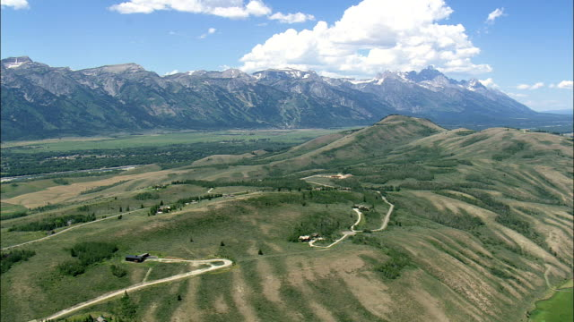 approaching teton village  - aerial view - wyoming,  teton county,  helicopter filming,  aerial video,  cineflex,  establishing shot,  united states - grand teton national park stock videos & royalty-free footage