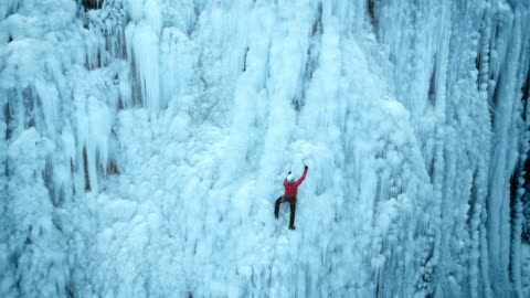 vídeos y material grabado en eventos de stock de acercarse al escalador de hielo en la empinada pendiente - deporte de riesgo
