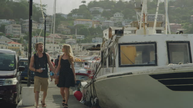 vídeos de stock, filmes e b-roll de approaching tourist couple holding hands and walking on waterfront near boat / st. georges, grenada - plano americano