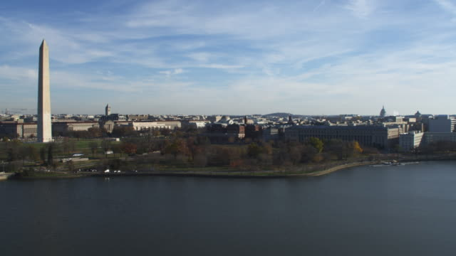 approaching washington dc over the tidal basin; washington monument slides out of frame at left, smithsonian buildings appear in mid-frame. shot in 2011. - smithsonian institution stock videos & royalty-free footage