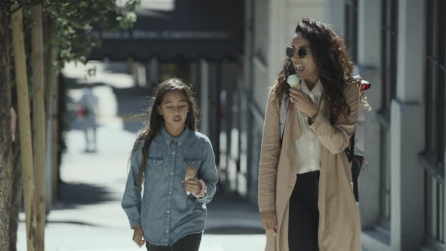 approaching woman and daughter walking uphill eating ice cream cones / san francisco, california, united states - approaching stock videos & royalty-free footage