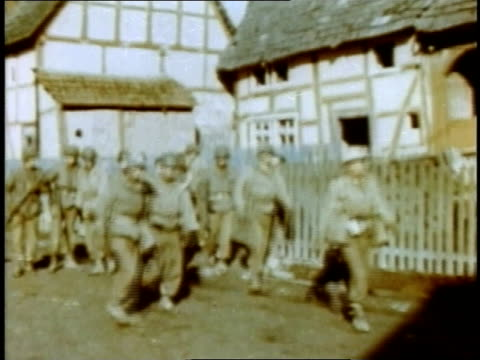 April 05 1945 MONTAGE Civilians gathering to watch American soldiers marching through village / Germany