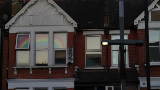 a picture of a rainbow and message thanking the nhs in a window the coronavirus pandemic has spread to many countries across the world claiming over... - nhs stock-videos und b-roll-filmmaterial