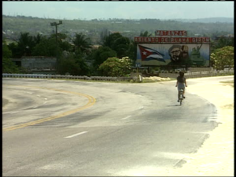april 1, 1994 bicycle rider and vehicle traffic passing by large rural roadside billboard displaying images of fidel castro, the national flag and a... - male likeness stock videos & royalty-free footage