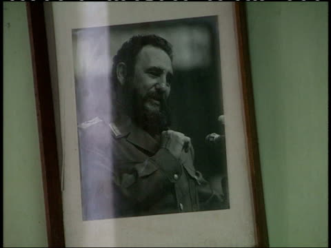 stockvideo's en b-roll-footage met april 1, 1994 framed photograph of fidel castro hanging crookedly on wall in sewing factory with two workers sitting at workstations sewing and... - mannelijke gelijkenis