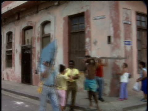 april 1 1994 montage passing by residents and pedestrians in urban area of rundown buildings and structural ruins / havana cuba - anno 1994 video stock e b–roll