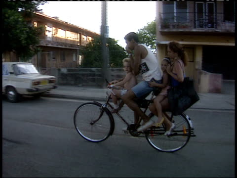 April 1 1994 TS Parents with their two small children together riding a bicycle pedaling down residential neighborhood street / Cuba