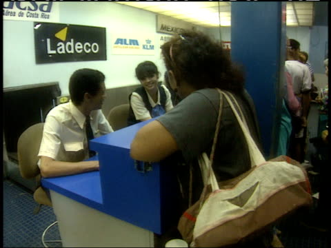 april 1 1994 ms passenger standing at ticket counter talking with airline agent in busy airport / cuba - airline check in attendant stock videos & royalty-free footage