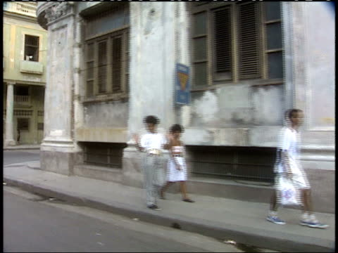april 1 1994 side pov pedestrians walking down sidewalks passing by rundown buildings in commercial area / havana cuba - anno 1994 video stock e b–roll