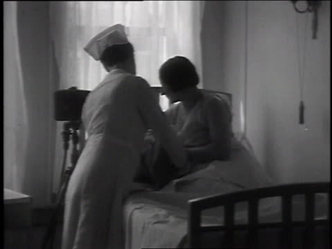 april 10, 1935 montage nurse giving woman a baby and asking how she looks / brooklyn, new york, united states - 1935 stock videos & royalty-free footage