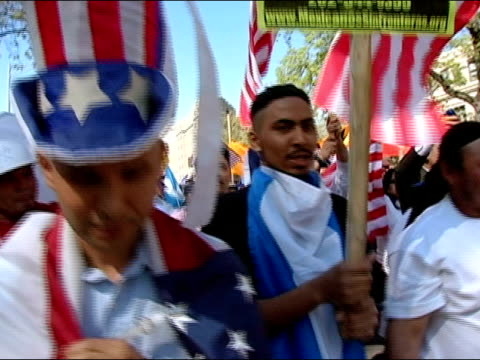 vídeos y material grabado en eventos de stock de april 10, 2006 medium shot demonstrator wearing 'uncle sam' hat draped in the american flag at the immigration rights march to the national mall /... - sombrero de copa