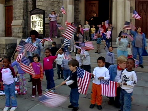 April 10 2006 Wide shot preschoolers holding American flags on steps of church during the immigration rights march to the National Mall / Washington...