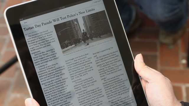 April 10 2010 CU screen of Apple iPad as person reads New York Times / views article and photograph / Washington DC