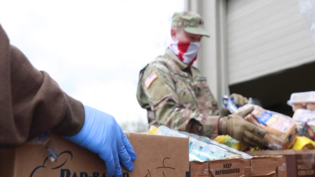 april 13, 2020 - ellettsville, indiana usa: members of the indiana national guard wear balaclava's while helping support volunteer workers... - giving stock videos & royalty-free footage