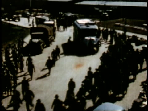 april 16 1945 montage locals getting off buses and moving through buchenwald / weimar thuringia germany - campo di concentramento di buchenwald video stock e b–roll