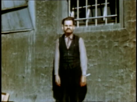 april 16 1945 montage man standing in front of window at buchenwald concentration camp / weimar thuringia germany - campo di concentramento di buchenwald video stock e b–roll