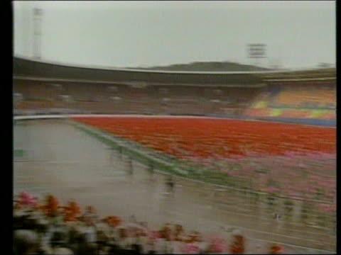 april 16 1992 film montage ms cheering crowd/ pan ws celebration in stadium for kim ilsung's 80th birthday/ ms kim ilsung waving to crowd/ ws... - människolem bildbanksvideor och videomaterial från bakom kulisserna