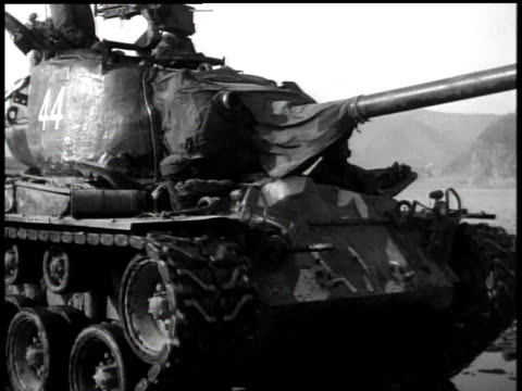 april 17, 1951 men riding on tank moving through mud / korea - 1951点の映像素材/bロール