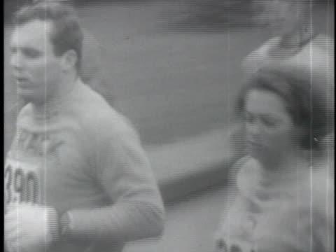 vídeos de stock e filmes b-roll de april 19 1967 film montage ms pan men surrounding katherine switzer first woman to run in the boston marathon/ ms switzer running/ boston... - boston massachusetts