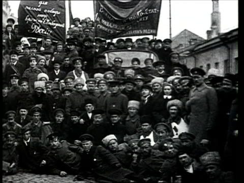 april 1917 montage b/w ms pan tu people gathered at demonstration in st. petersburg street following february revolution, holding 'land and liberty' banners/ ws demonstrators travelling past in trucks and cars/ st. petersburg, russia - cyrillic script stock videos & royalty-free footage