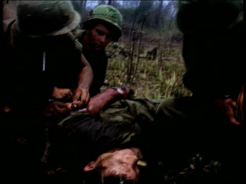 april 1967 montage a casualty is treated on the battlefield and carried to waiting helicopter / vietnam - battlefield stock videos & royalty-free footage