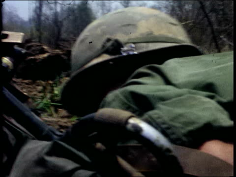 april 1967 montage soldiers crouching low, crawling through field of combat during enemy fire / vietnam - 南ベトナム点の映像素材/bロール