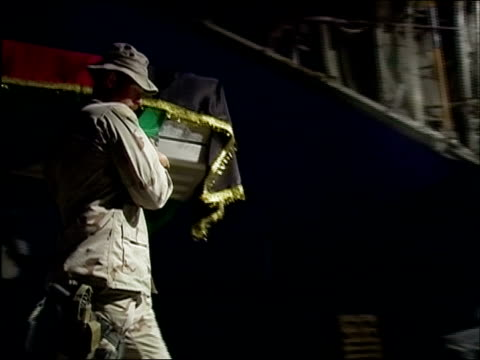 April 2004 Afghan National Army and American soldiers carrying flagdraped coffin of dead ANA soldier onto US C130 Hercules at night as flashes from...
