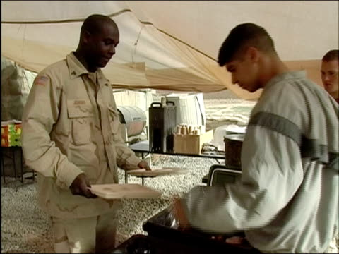 april 2004 american soldiers moving down serving line under mess tent at camp tiger / ghazni afghanistan - 盆点の映像素材/bロール