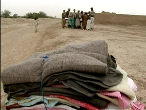 april 2004 bundle of blankets donated by us army lying on dirt road / tilt up to crowd of men and boys gathered to look at something in background /... - kandahar afghanistan stock videos & royalty-free footage