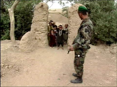 April 2004 children gathered at gate guarded by Afghan National Army soldier looking at camera and laughing / Kandahar Province Afghanistan
